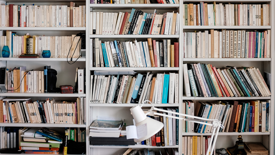 Three column bookshelf full of many books. A white lamp is sitting in front of the bookcase.