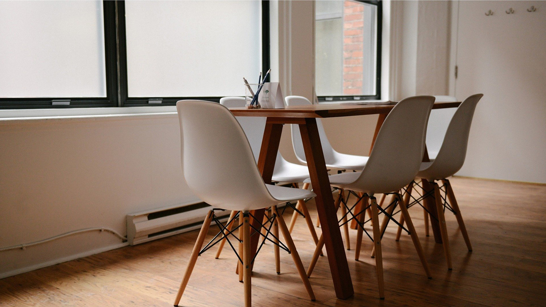 Mid-century modern style wooden table with 6 white chairs. A container with 3 pencils is sitting on top.